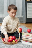Boy with apples and books  at home Royalty Free Stock Photography