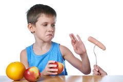 Boy with apples and orange against harmful sausage Royalty Free Stock Photography