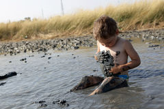 Boy applying black healing clay. In Primorsko-Akhtarsk, Russia royalty free stock photography