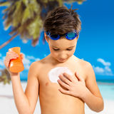Boy applying sun block cream on the tanned body Stock Image