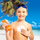 Boy applying sun block cream on the tanned body Stock Photography