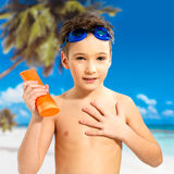 Boy applying sun block cream on the tanned body Stock Photos