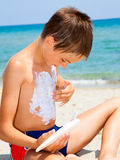 Boy applying sunscreen Royalty Free Stock Photography