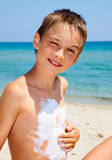 Boy applying sunscreen Stock Photos