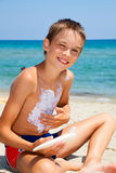 Boy applying sunscreen Stock Images