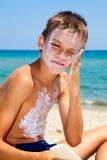 Boy applying sunscreen stock image