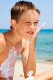 Boy applying sunscreen Royalty Free Stock Image