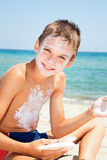 Boy applying sunscreen. Child applys too much of sunblock cream Royalty Free Stock Images