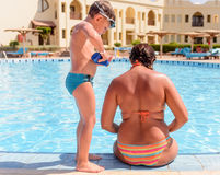 Boy applying sunscreen to his mothers back Stock Image