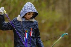 Boy archer shooting with his bow at an outdoor Stock Photos