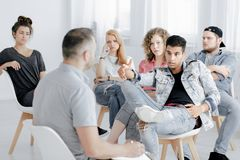 Boy arguing with therapist. Teenage boy in denim jacket arguing with therapist during group psychotherapy Stock Photography