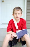 Boy with arm in a sling from a broken humerus. A sad young boy sits on his front porch with a broken arm stock images