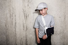 Boy with arm in a sling from a broken humerus wearing a baseball Stock Photos