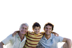 Boy with arms around father and grandfather, smiling, front view, portrait, cut out Royalty Free Stock Images
