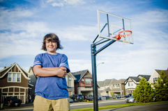 Boy with arms crossed with basketball net smiling Royalty Free Stock Image