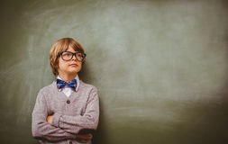 Boy with arms crossed looking up at blackboard. Cute little boy with arms crossed looking up at blackboard Royalty Free Stock Photography