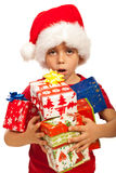Boy with arms full of Xmas gifts. Amazed boy with Santa hat having arms full of Christmas gifts isolated on white background Royalty Free Stock Images