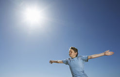 Boy With Arms Outstretched Against Sky Royalty Free Stock Photo