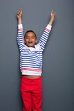 Boy with arms raised and pointing up Stock Images