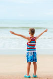 The boy with arms stretched out to the sides rests Stock Photos