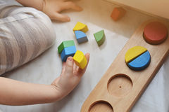 The boy arranges geometric wooden figures. Concept education. Royalty Free Stock Image