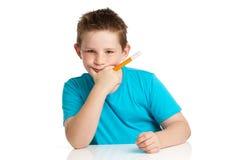 Boy Artist. Thinking with felt pen in hand. Studio white background Stock Photo