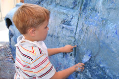 Boy artistically paint car. A little boy paints a small car blue as an art project Royalty Free Stock Images