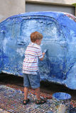 Boy artistically paints car. A little boy paints a small car blue as an art project Stock Photos