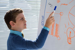Boy as business executive presenting on white board Royalty Free Stock Photos