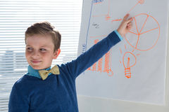 Boy as business executive presenting on white board Stock Photography