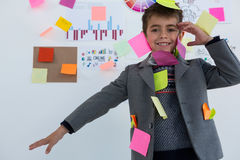 Boy as business executive with sticky notes on his body. In office Stock Images