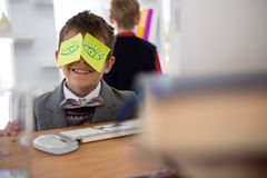 Boy as business executive with sticky notes on his eyes. Boy as business executive with sticky notes on his face in office royalty free stock images