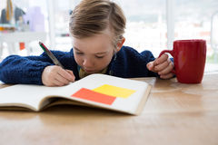 Boy as business executive writing in a book Stock Image