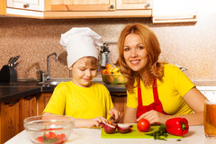 Boy as chef cutting vegetables with mother Stock Images