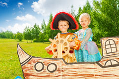 Boy as pirate holds helm and princess girl Royalty Free Stock Image