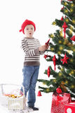 Boy as Santa helper decorating Christmas tree Royalty Free Stock Photo