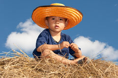 Boy of Asia sit on straw. Little boy with hat and sunny weather Stock Images