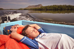 Boy Asleep on Boat - Monte Cristi, Dominican Republic. Young boy basks in warm glow of tropical sun on a blue boat Stock Photo
