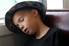 Boy Asleep In Booth. Sleeping boy sitting up in a restaurant booth with his head leaning against the window sill beside him Stock Photo
