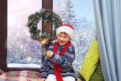 Boy asleep on Christmas night .Boy in Santa hat sleeping on the windowsill Royalty Free Stock Photography