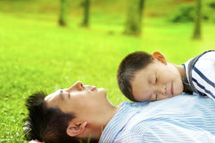 Boy asleep on dad's chest. Boy lying on father. Father lying on green grass outside Royalty Free Stock Image