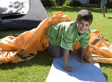Boy (8-10) assembling dome tent on garden lawn, kneeling on roll mat beside outer tent canvas, smiling, portrait Royalty Free Stock Photography