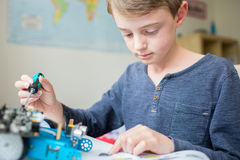 Boy Assembling Robotic Kit In Bedroom Stock Photos
