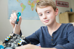 Boy Assembling Robotic Kit In Bedroom stock photo