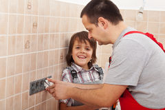 Boy assisting his father installing electical outlets Royalty Free Stock Images