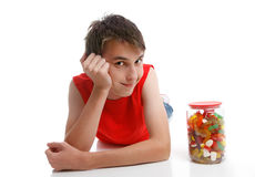 Boy beside an assortment of mixed confectionery. A smiling boy beside a jar of mixed soft sweet candies. White background royalty free stock images