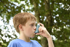 Boy with Asthma inhaler. Young boy using a blue asthma inhaler stock images