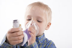 Boy with asthma inhaler. Young boy using an asthma inhaler, white background Royalty Free Stock Photography