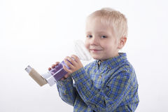 Boy and asthma inhaler. Young boy using an asthma inhaler, white background royalty free stock photo