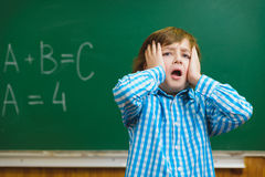 Boy with astonished expression on blackboard background . Educational and school concept Royalty Free Stock Image